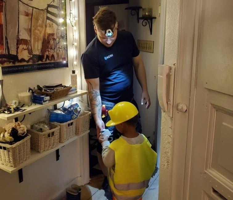 Nicolai låsesmed i Brønshøj arbejder også som autoriseret elektriker og viser en dreng nogle reservedele